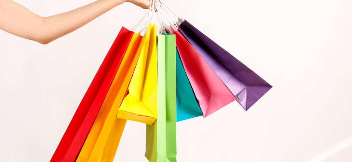 Womens arm holding colourful shopping bag on a cream background